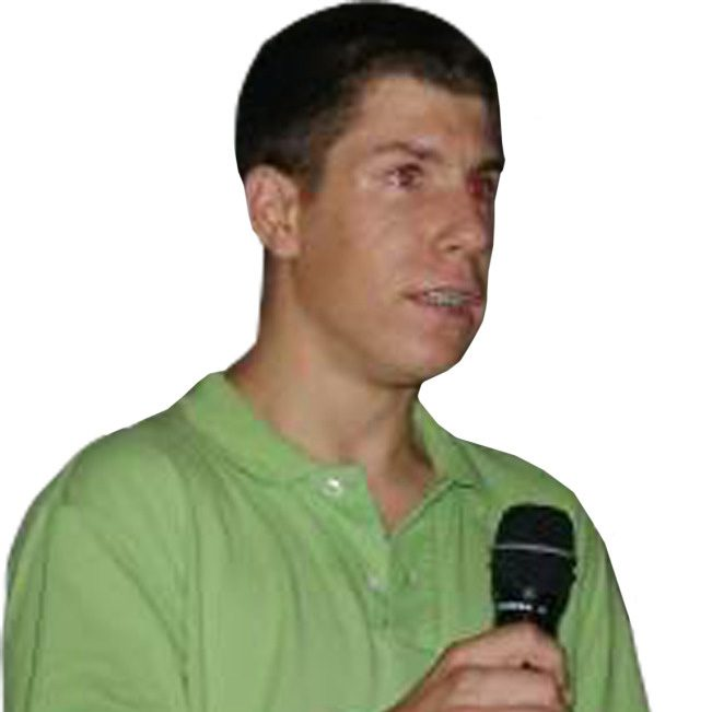 Young man in green shirt holding a microphone.