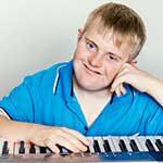 Man sitting at a keyboard and smiling at the camera.